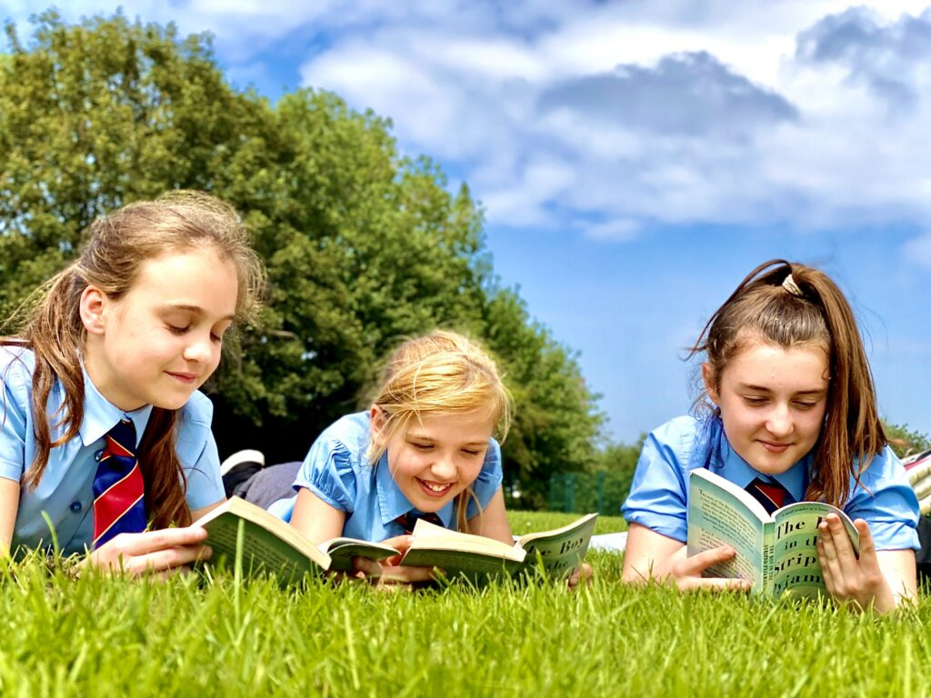 pupils reading books outdoors